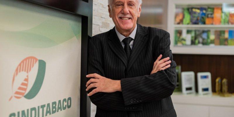 Homem de cabelo branco e bigode branco, com terno e gravata, encostado em uma placa escrito SindiTabaco