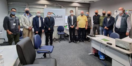 Onze homens usando máscara e um banner do Sinplast-RS ao fundo. Cadeiras cinza e azul e mesa bege